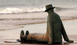 Statue showing man sitting on beach looking out to the sea